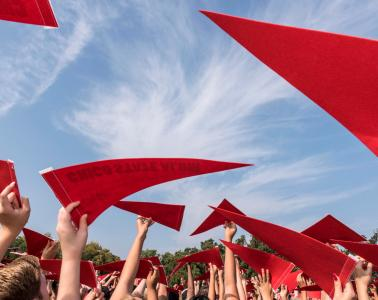 New students hold Alumni pennants as they look to the sky to have their photo taken by a drone as they participate in the Big C Welcome Ceremony during the Wildcat Welcome on Friday, August 21, 2015 in Chico, Calif.  (Jason Halley/University Photographer)