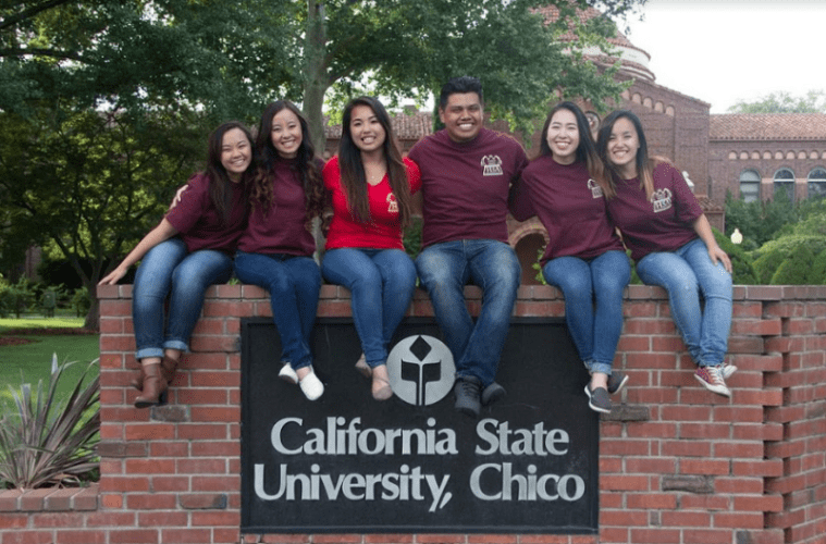 A group of students sits on top of the California State University, Chico sign.