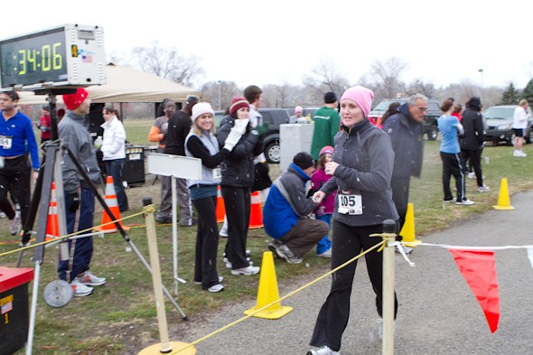 Amy Gorman crosses the finish line of the 2010 Cooper River Turkey Trot for Breast Cancer only months after her own surgery while her family cheers her on behind.