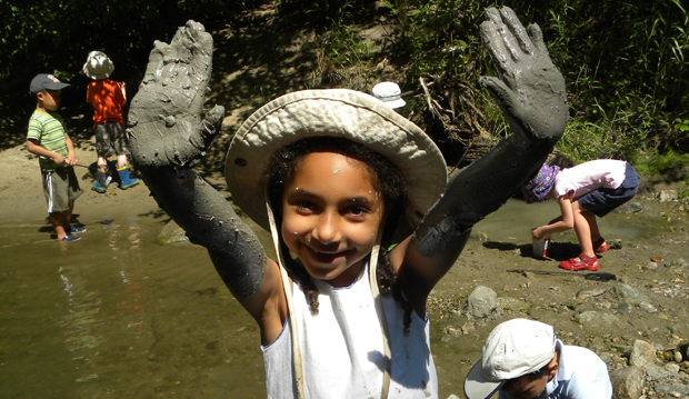 kids with girl and muddy hands by river