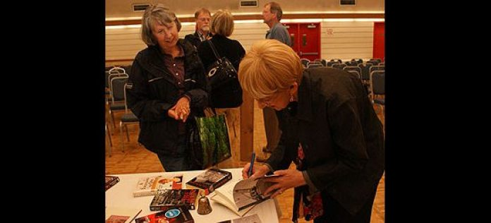 Nina Kootnekoff looks on as mystery novelist Rosemary Aubert signs a copy of her latest book, The Judge of Orphans, for her.