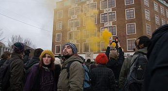 Two protesters look out as a police smoke canister sets off behind them.