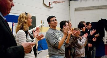 Parents clap after students perform a song.