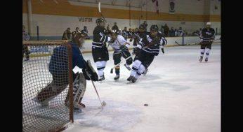 King Academy's Phil Janovski #5 pushes through two Porter defensemen. Eagles goaltender, Keagan Chmara plays the puck.
