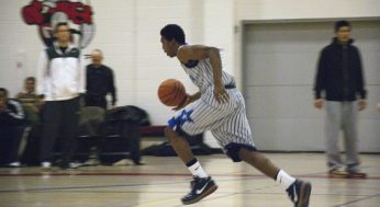 Laurier player, Daniel Mullings #22, intercepts a pass just over half-court, and breaks down the hardwood to gain two points for his team.
