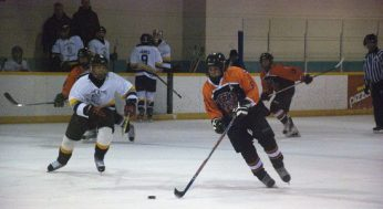Bendale's assistant captain, Ryan Burtt #8, wheels through the neutral zone. King Academy's Fischer, chases him.