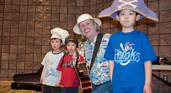 Jim Parker and several children pose for a photo dressed in crazy hats after a performance at the Malvern Public Library