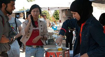 Volunteer Anum Butt prepares a cob of corn to give to a UTSC student at the market.
