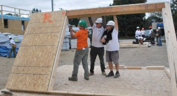Volunteers work in groups to get parts of the house ready