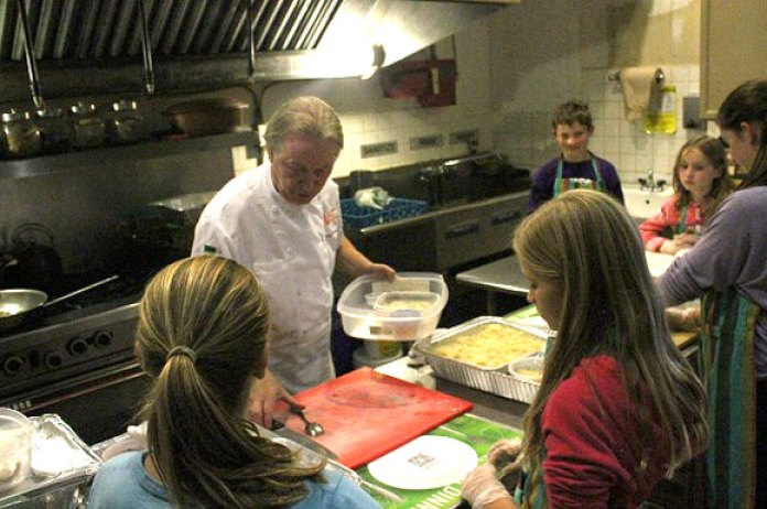 Chef Heinz J. Lehmann walks young volunteers through various aspects of cooking at a recent Kids Cook To Care (KCTC) community meal at the Christie Ossington Neighbourhood Centre on Bloor Street West. KCTC is a charitable initiative that encourages kids age six to 16 years old to learn about different cultures and the importance of giving back to their community through cooking.