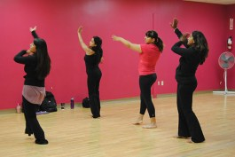 Sheetal enthusiastically leads a warm-up with three students from the BollyFuze Class.