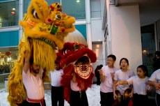 The Hung Moon lion dance troupe performs in front of HSBC outside Chinatown Centre near Spadina Avenue and Sullivan Street. The group consists of volunteers ranging from elementary school students to adults.