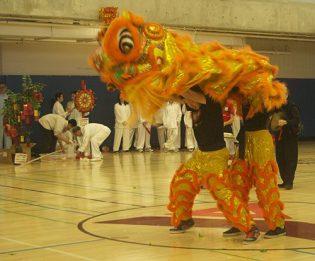 Orange dragon dancers display enthusiasm and excitement.