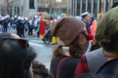 An onlooker wears a red nose to support the holiday season.