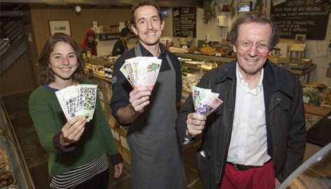 """Peter Main (right), mayor of Bristol, shows a handful of Bristol pound notes, an initiative to stimulate the local economy under the theme """"our city, our money"""". Main receives his paycheck as mayor in Bristol pounds. Photo: Bristol City Council"""