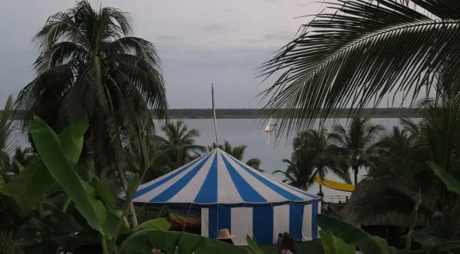 "Cayuco Maya, the venue for the XV Vision Council, ""Call of the Water,"" was held on the shores of Bacalar Lagoon. Foreground: The Circus Tent has been a trademark gathering space for two decades in Vision Councils from Peru to Mexico."
