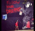 Picture of Robin Arzon with Wall that says Follow Your Dreams