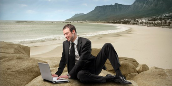 businessman in suit with laptop on beach
