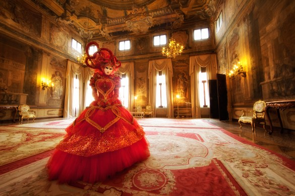 Gorgeous Carnival model in red inside a Venetian palace