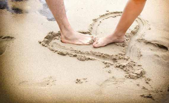 couples feet in sand