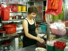 A woman prepares dinner in her Singapore streetside joint.