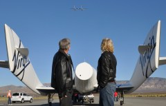 Sir Richard Branson (R) and designer Burt Rutan stand behind SpaceShip2 just after its successful landing in Mojave, Ca. Flyin overhead is the WhiteKnight2- or mothership that carried the spaceship aloft. The craft was piloted by engineer and test pilot Pete Siebold from Scaled Composites. Photo: Mike Mills
