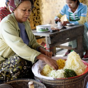A Burmese woman makes a tofu salad to order on the steps to one of Bagan's many temples.