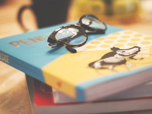 Eye glasses sitting on top of a book.