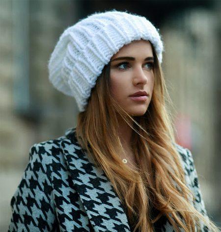 Пальто в сочетании с белой вязаной шапкой на девушке