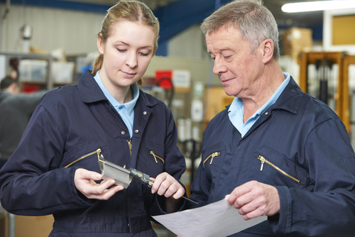 Young woman and older man examine a component in a factory