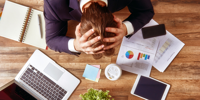businessman in panic. a young man sits at his Desk and holds his hands on his head.