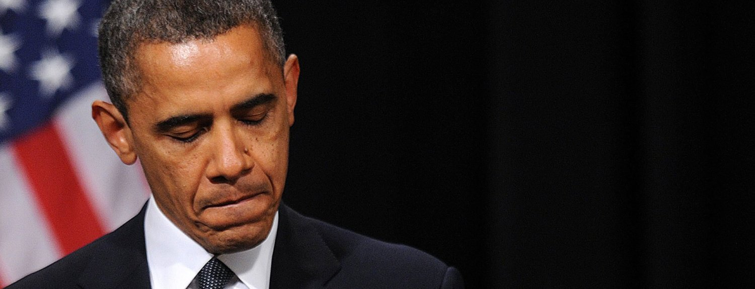 """U.S. President Barack Obama pauses during a speech at a memorial service for victims of the Sandy Hook Elementary School shooting at Newtown High School in Newtown, Connecticut, U.S., on Sunday, Dec. 16, 2012. Obama said that the nation was """"left with some hard questions"""" in the aftermath of the massacre at Sandy Hook Elementary school in Newtown, Connecticut, while promising the community to help itself heal. Photographer: Olivier Douliery/Pool via Bloomberg *** Local Caption *** Barack Obama"""