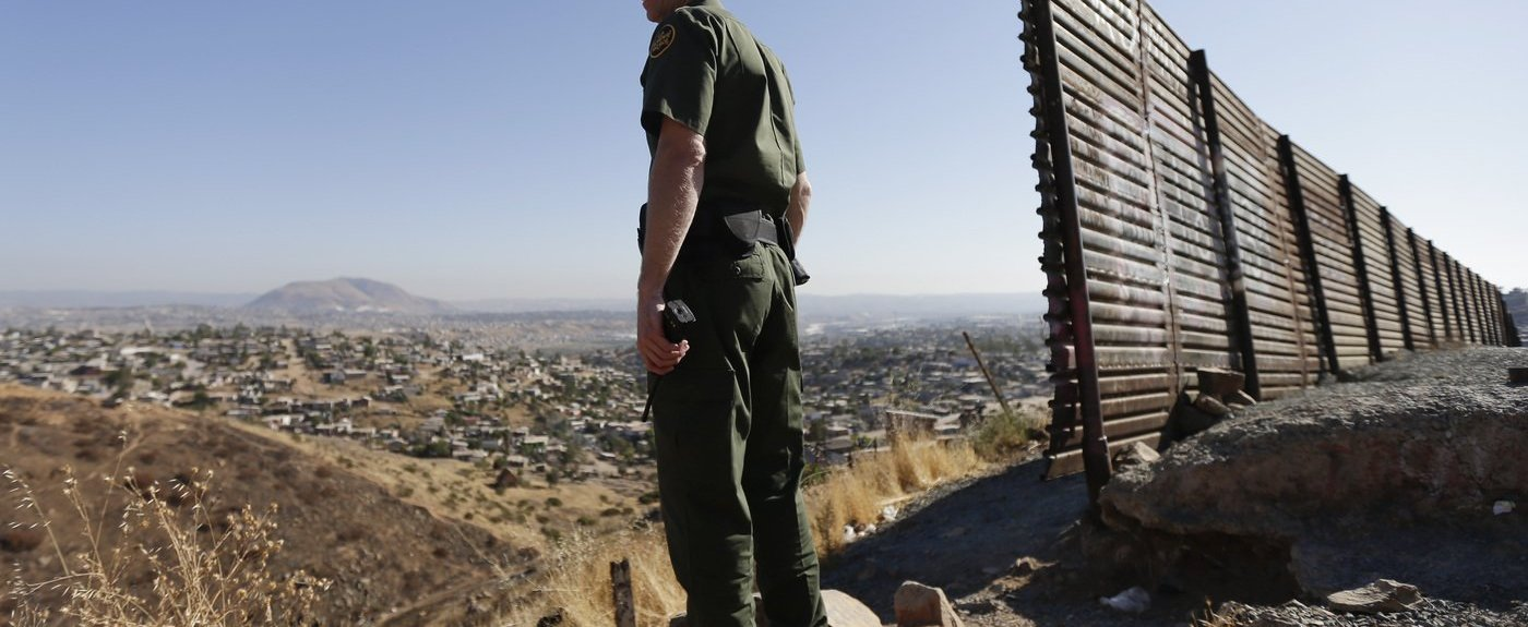 AU.S. Border Patrol agent looks out over Tijuana, Mexico, next toa portion of the U.S.-Mexico border wal