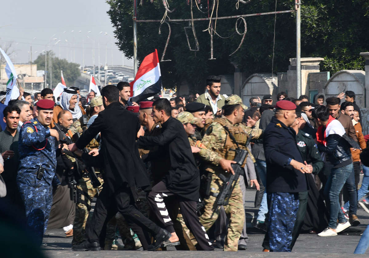 """Iraqi protesters in the southern Iraqi city of Nasiriyah clash with supporters of Iraq's pro-Iranian paramilitary group Hashed Al-Shaabi on January 5, 2020, denouncing both the U.S. and Iran as """"occupiers"""" while demanding reforms within their own government."""