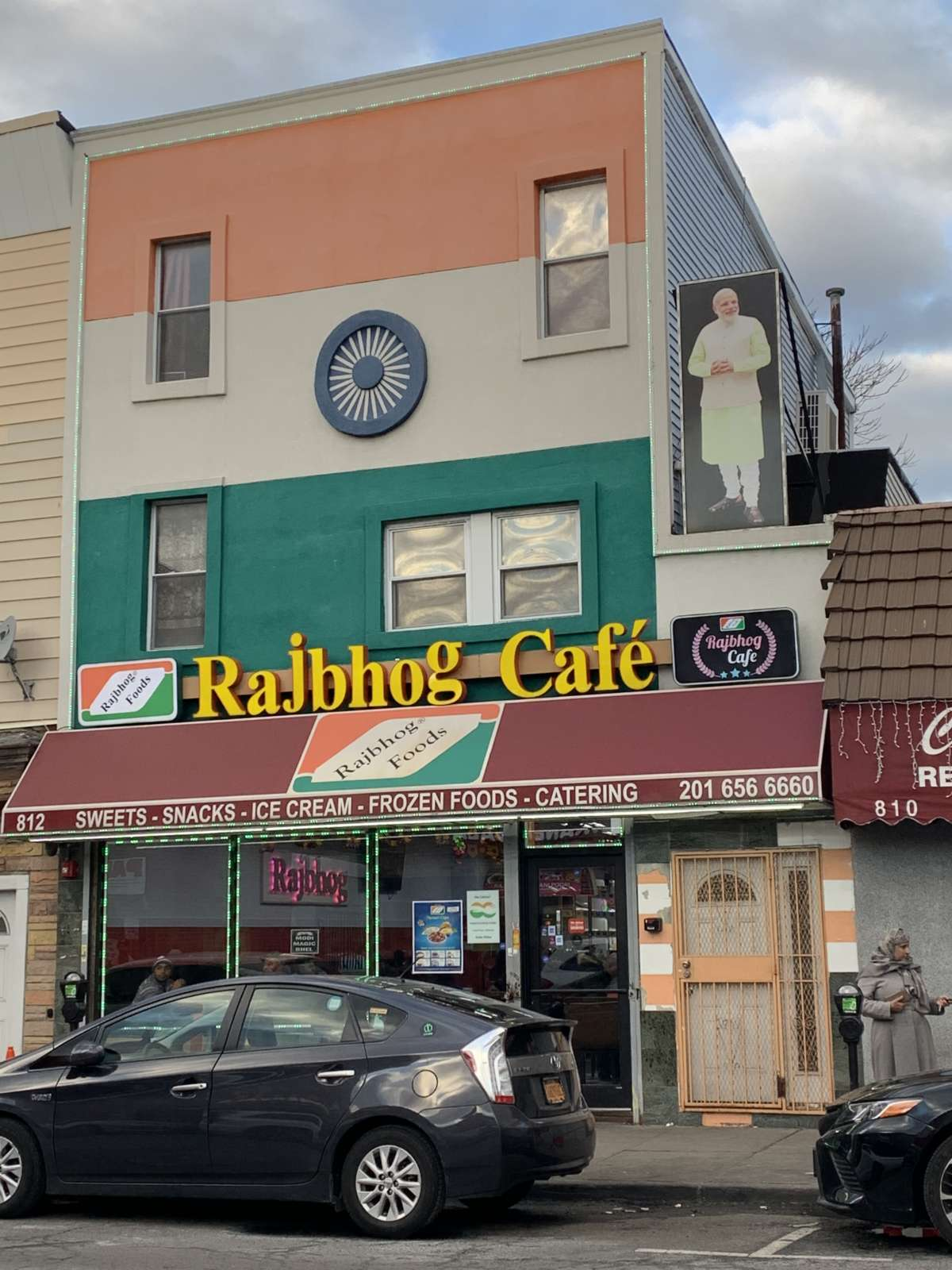 Rajbhog Cafe on Newark Avenue, Jersey City, NJ, where a large picture of a picture of Narendra Modi is hung above.
