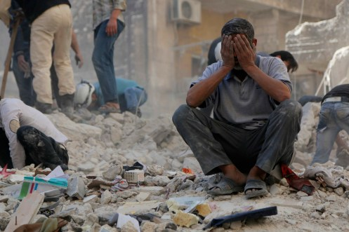 A man reacts amid debris after what activists said were explosive barrels thrown by forces loyal to Syria's President Bashar al-Assad in Al-Shaar neighbourhood of Aleppo April 27, 2014. REUTERS/Hosam Katan (SYRIA - Tags: POLITICS CONFLICT TPX IMAGES OF THE DAY) - RTR3MTUG