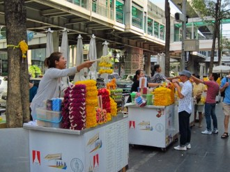 January- Flower hawker outside Erawan Shrine on New Years Day, Bangkok, Thailand
