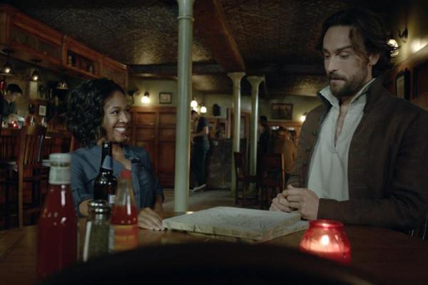 "Ichabod (Tom Mison) and Abbie (Nicole Beharie) share drinks in the Sleepy Hollow, season premiere, ""I, Witness."""
