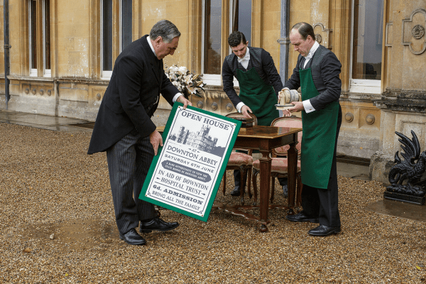 Mr. Carson and other servants put up an open house sign at Downton Abbey