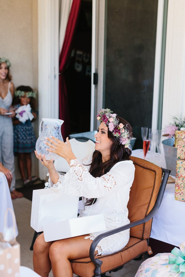 A Flower Crowns & Champagne Backyard Bridal Shower | Ultimate Bridesmaid | Dulcet Creative | Bride opening gifts at her bridal shower