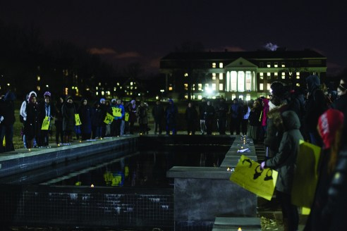 Dozens of students came together on McKeldin Mall Feb. 12 to commemorate the lives of the three individuals slain in the Chapel Hill shooting last week.  James Levin/The Diamondback