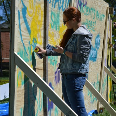 Freshman nursing student Elisheva Glicksman spray paints the back of a mural created by Artists 4 Israel. Dovid Fisher/Mitzpeh