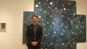 "Brian Hitzelberger stands beside his piece ""Night Mind"" in the Bob Owens Art Gallery."