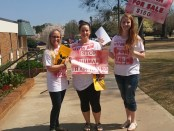 Emily Drew and other students show off the shirts and signs made for the protest. (Photo by Victoria Cochran)