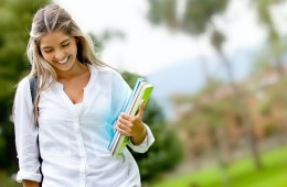 Shy female student walking outdoors and smiling