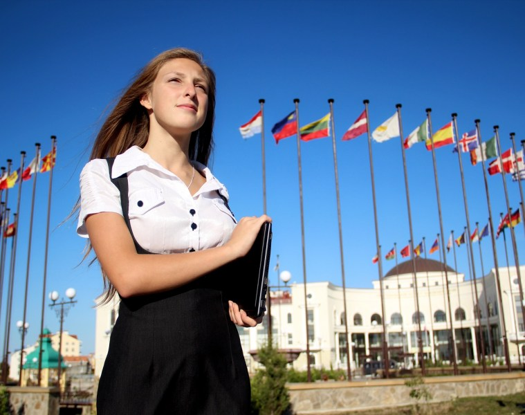 girl student on the background of international flags in the wind