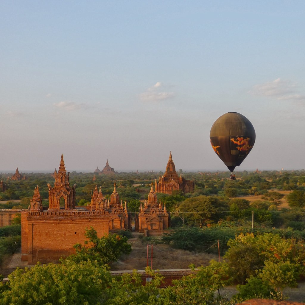 Tourists in a hot air balloon drift at sunset over the pagodas of Bagan
