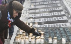 A Holocaust survivor places a lit candle at the Monument of the Victims during ceremonies to mark the 69th anniversary of the liberation of Auschwitz Nazi death camp's in Oswiecim, Poland, on Monday, Jan. 27, 2014, after the Soviet Red Army liberated the camp. The Nazis killed some 1.5 million people, mostly Jews at the camp during World War II. (AP Photo/Czarek Sokolowski)