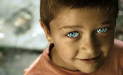 Bambino con viso poco pulito e grandi occhi blu