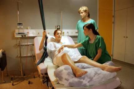 Una donna è in travaglio e viene aiutata a partorire